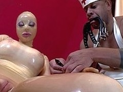 Latex Lucy is a fetish dame with big boobs and puffy pussy. She wears skin tight rubber suit. Shes in wheel chair while black man in uniform plays with her body.